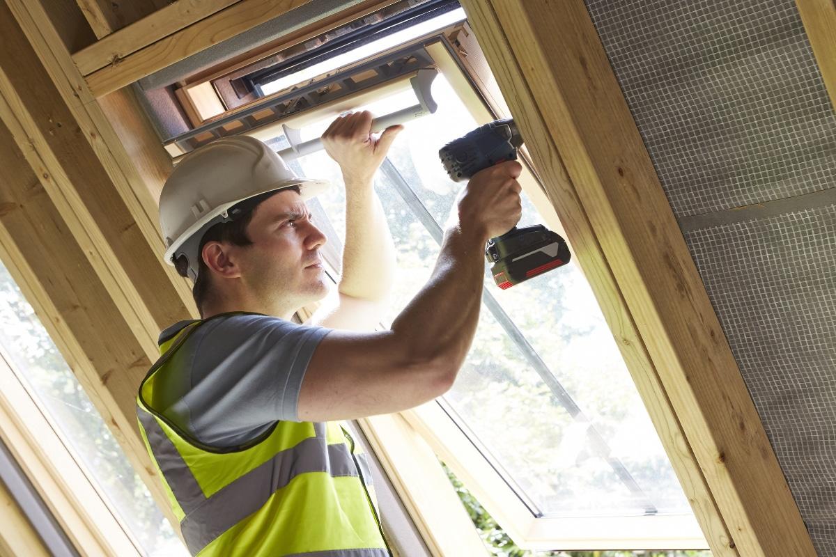 werkman die houten ramen aan het vervangen is